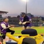 A woman runs away from her partner's marriage proposal at a baseball stadium
