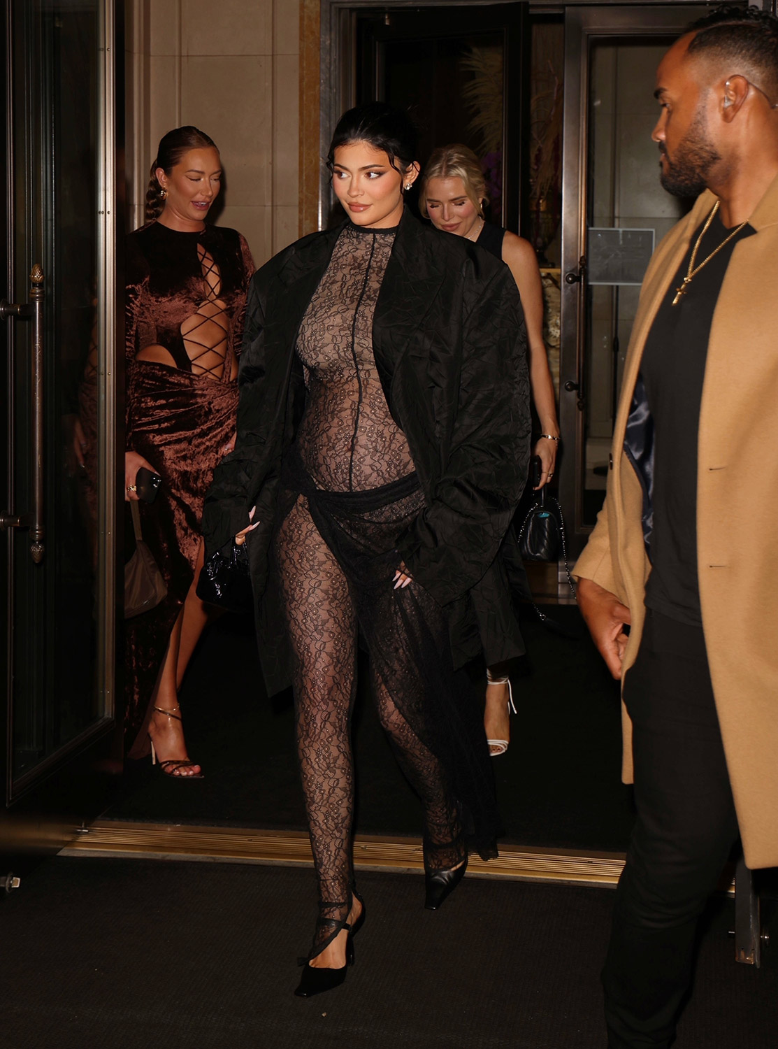 Pregnant Kylie Jenner shows off her belly in a sheer lace jumpsuit during NYFW