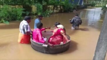 Desperate to get married, Indian couple floats in large pot to reach their wedding after flooding